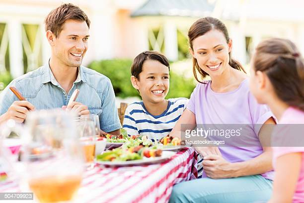 Family Having Meal At Outdoor Table