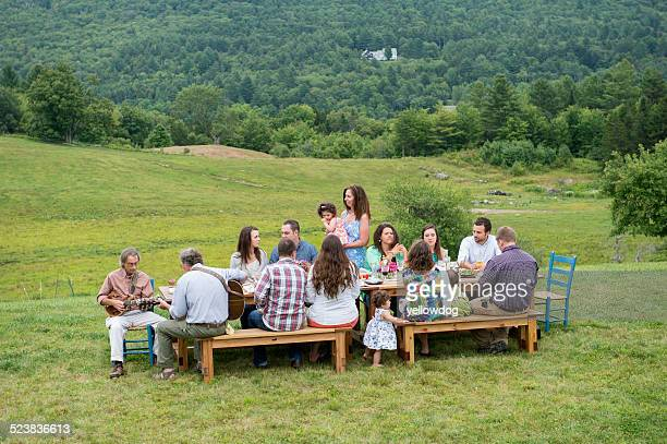 Family having meal together and socialising, outdoors