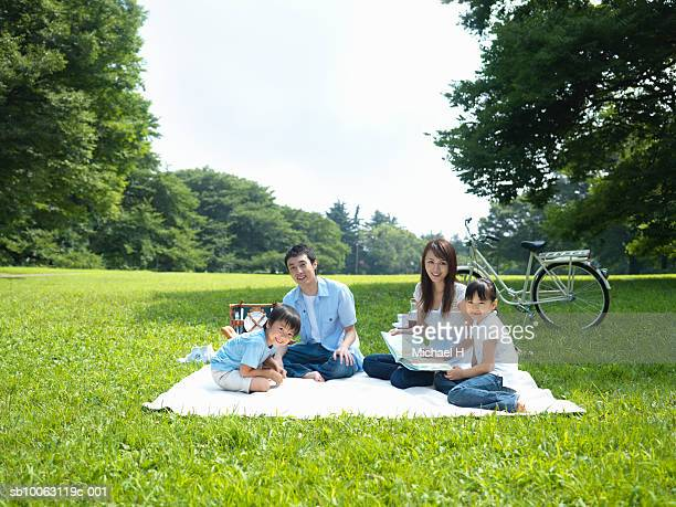 Family having picnic in park, smiling, portrait