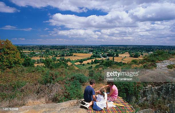 Family having picnic on Mont-Dol in Ile-et-Vilaine department with Mont St Michel in far background across fields.
