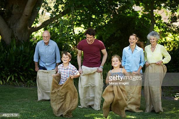 Family having sack race in park