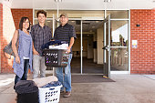 Family helping college student son move into dormitory