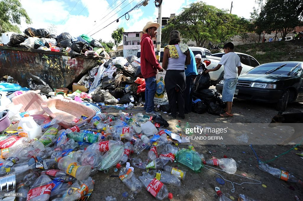 A family helps in the clean-up of the city to fight the Aedes Aegypti mosquito that transmits Zika virus, as well as viral diseases such as dengue and chikungunya, in Tegucigalpa on February 6, 2016. Honduras on Mondayy declared a state of emergency after officials said the number of Zika infections was rising at an 'alarming' rate in the Central American country. Since December 16, when the first case of the mosquito-borne virus was detected, there have been more that 4,000 cases of people infected with the virus in Honduras. AFP PHOTO / ORLANDO SIERRA / AFP / ORLANDO SIERRA