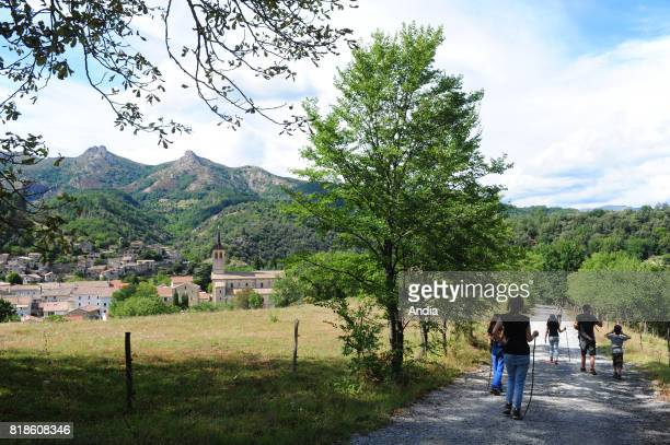 Family hike in the Regional Nature Park of Monts d'Ardeche near Jaurac Couple and children walking on a path and view of the village