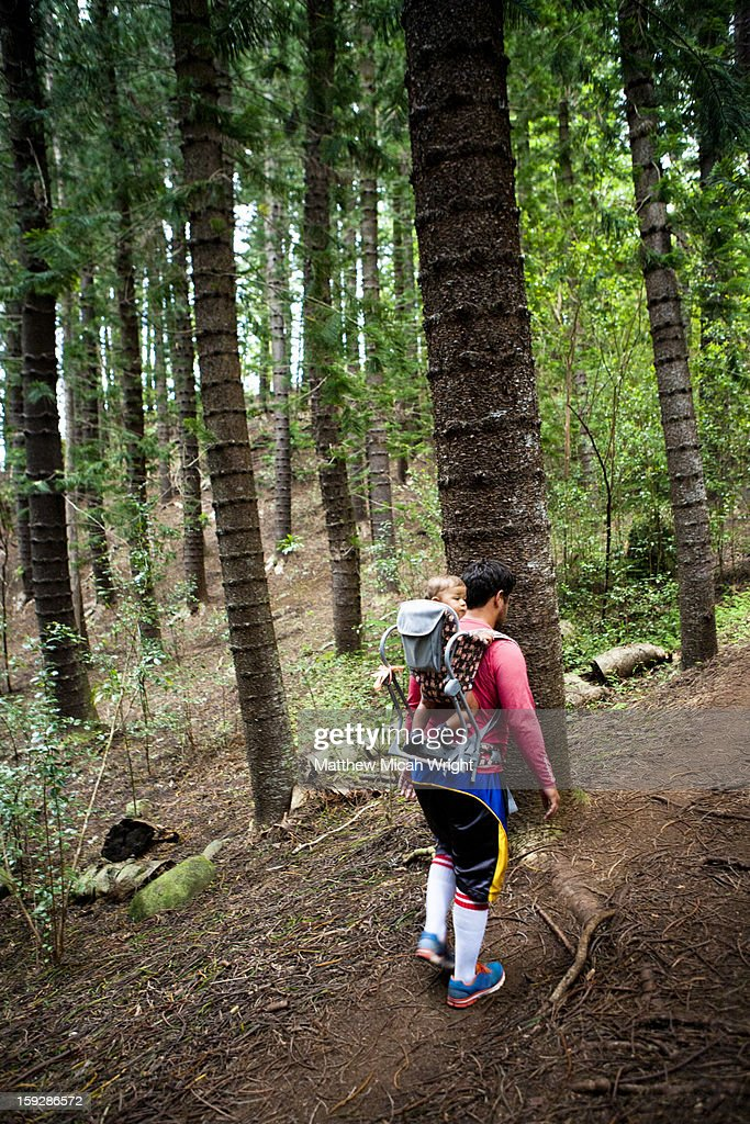 A family hikes through Norfolk pine trees : Stock Photo