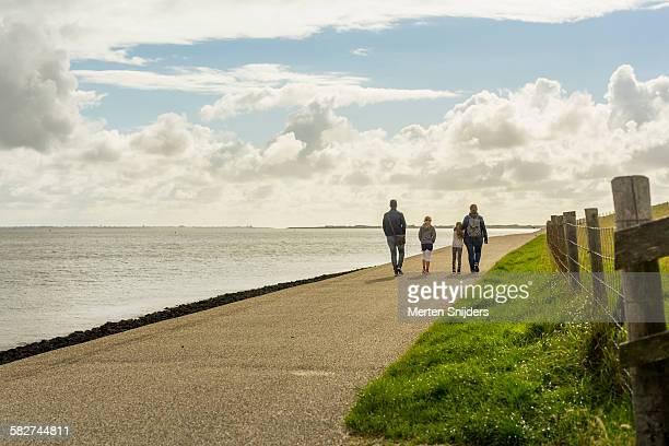 Family hiking along dyke and sea