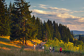Family hiking in the mountains on summer vacation at dusk