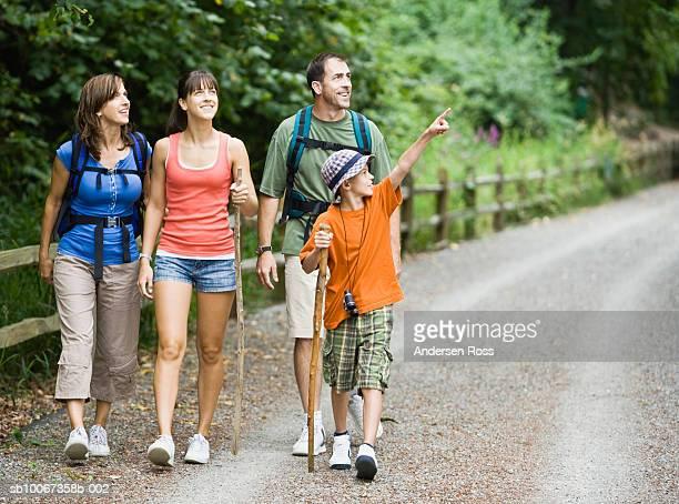 Family hiking through park, boy (10-11) pointing