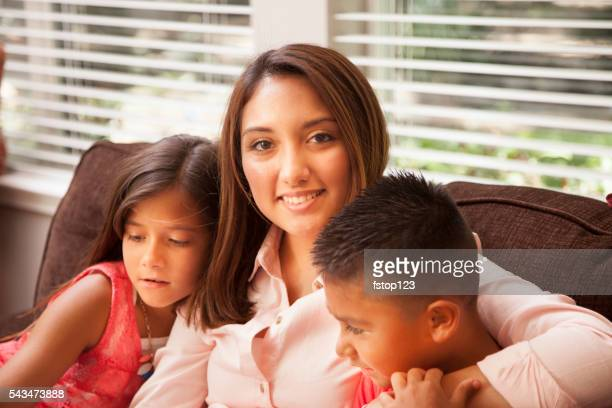 Family.  Hispanic mother and two children relaxing at home.