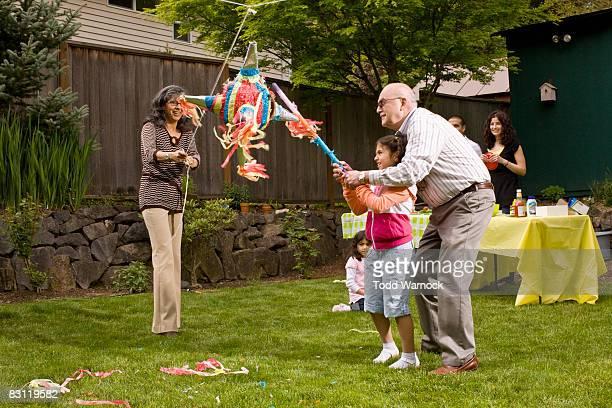 Familie schlagen Piñata
