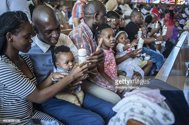 A family hold candle with their baby during Christmas mass held to commemorate the birth of Jesus Christ at the Regina Mundi Church the largest Roman...