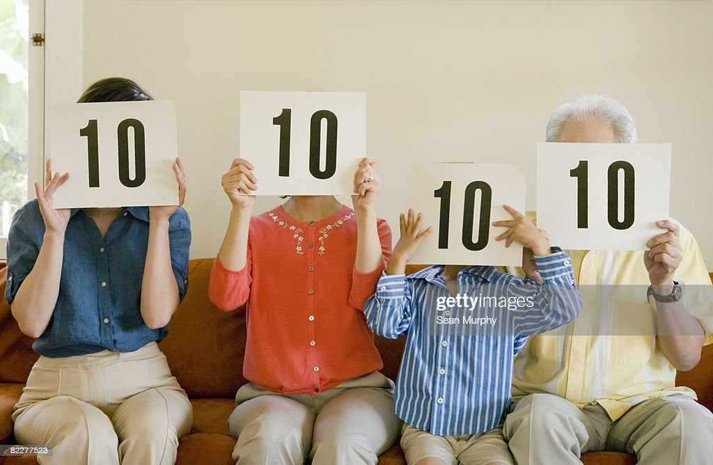 Family holding '10' cards in front of faces : Stockfoto