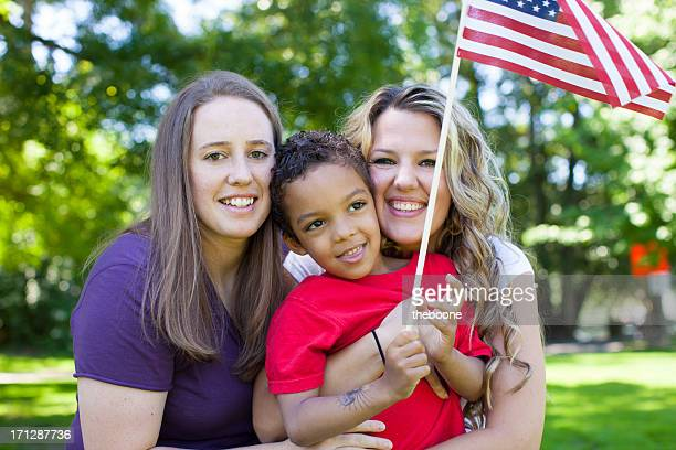 Family holding American flag in a park during summer