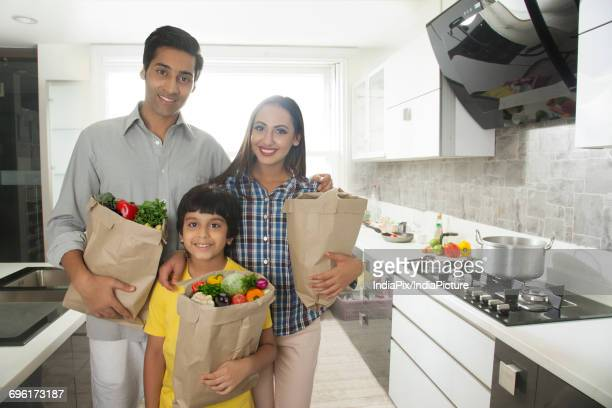 Family holding bags of groceries in kitchen