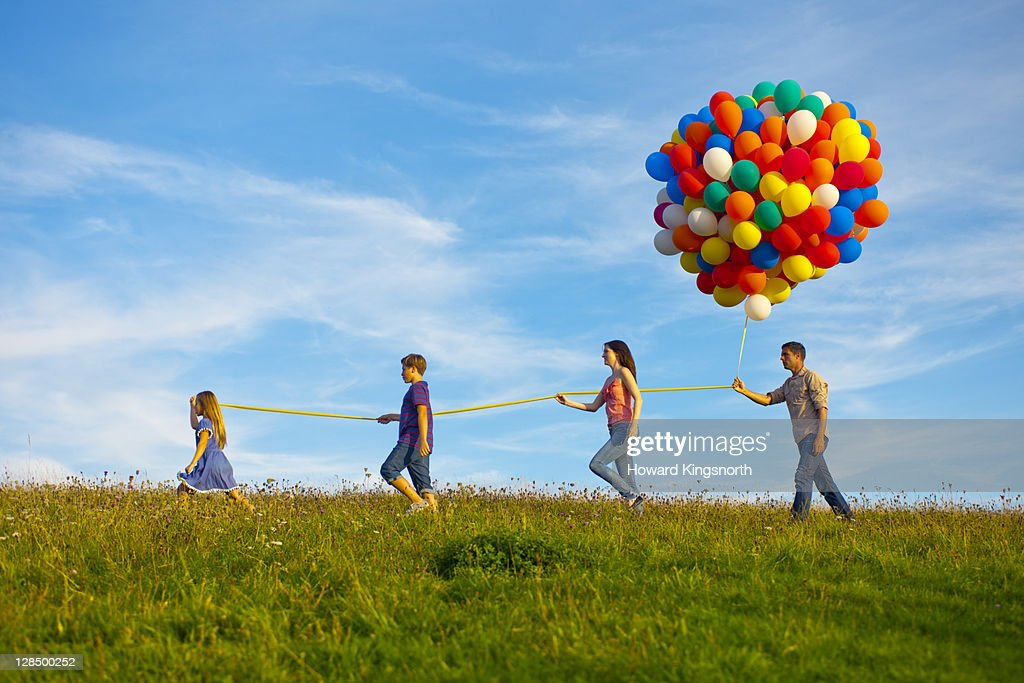 family holding big bunch of balloons : Stock Photo