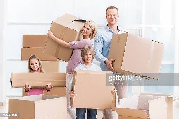 Family holding cardboard boxes and moving into a new house.