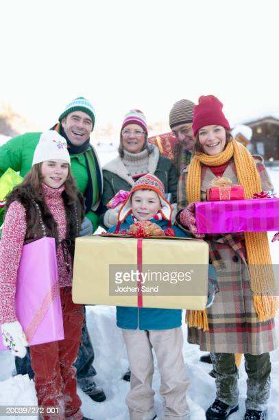 Family holding gifts standing in snow, smiling, portrait