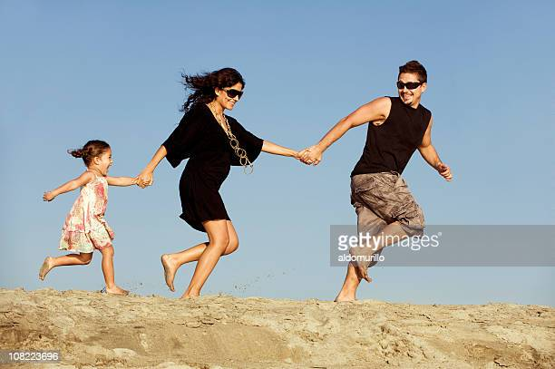 Family Holding Hands and Running in Sand on Beach