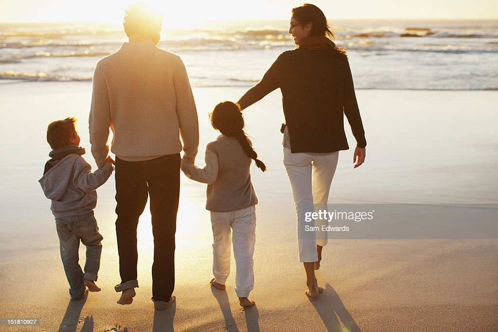 Family holding hands and walking on beach at sunset : Stock Photo