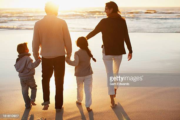 Family holding hands and walking on beach at sunset