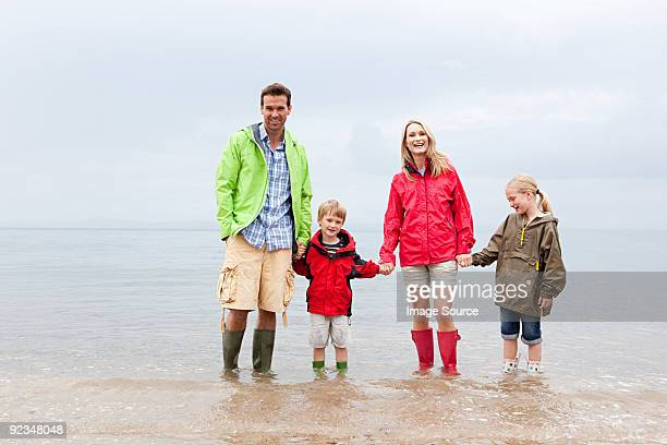 Family holding hands in the sea