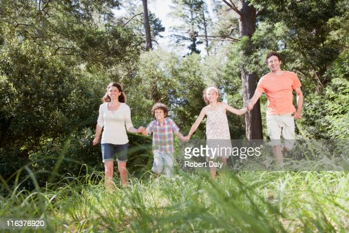 Family holding hands in woods