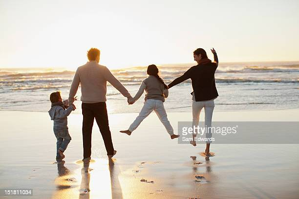 Family holding hands on beach at sunset