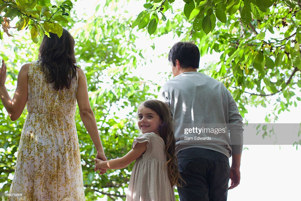 Family holding hands together outdoors : Stock Photo