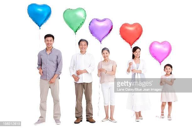 Family holding heart-shaped balloons