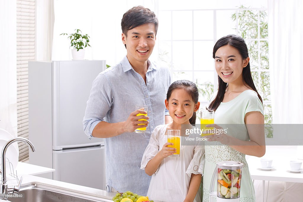 Family holding juice in kitchen : Stock Photo