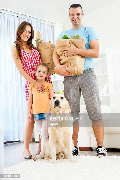 Family Holding Paper Shopping Bags with groceries.