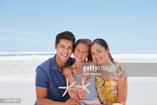 Family holding starfish on beach : Stock Photo