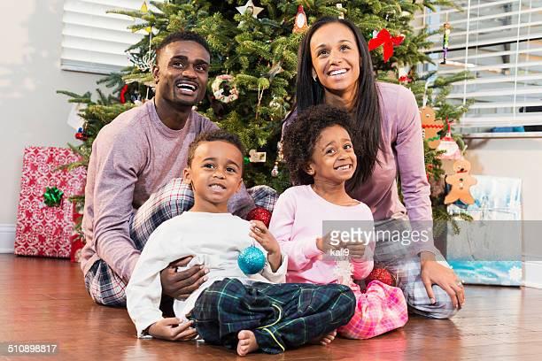 Ritratto di vacanza in famiglia, seduto davanti ad albero di Natale