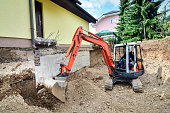 A big family house is being rebuilt with the help of an excavator. Digging the brick and concrete foundation for hydro isolation of basement.A big family house is being rebuilt with the help of an exc