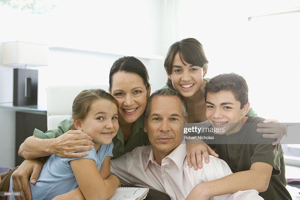 Family hugging and smiling : Stock Photo