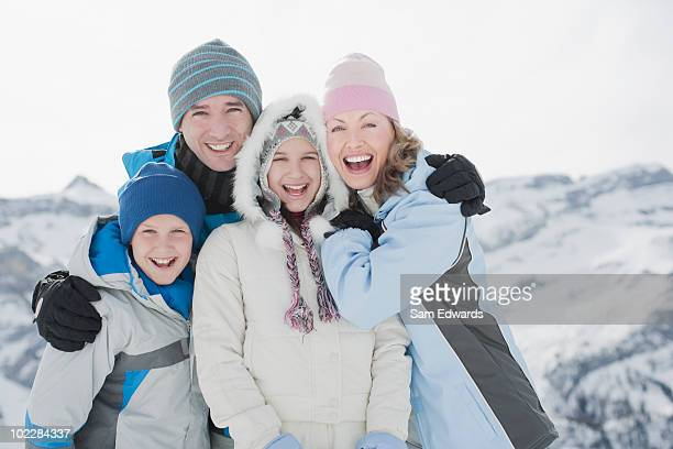 Family hugging outdoors in snow