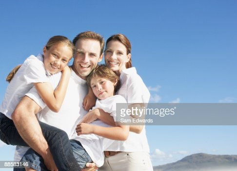 Family hugging outdoors : Stock Photo