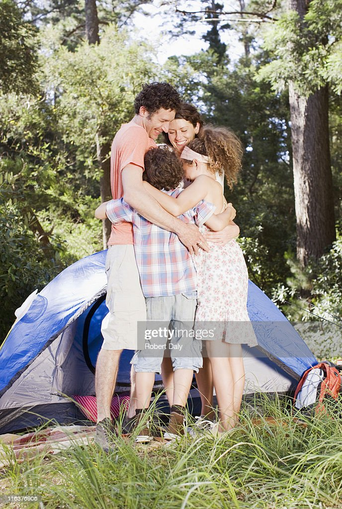 Family hugging outside tent : Stock Photo