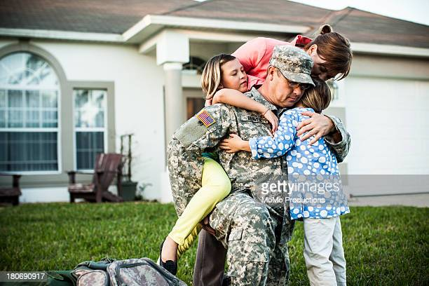 Family hugging soldier before deployment