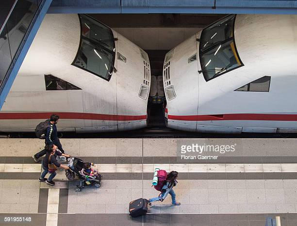A family hurries up to get into the train at the central station on August 19 2016 in Berlin Germany