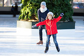 little boy learning ice skating and his mother watching and cheering up at outdoor skating rink, having winter vacation fun