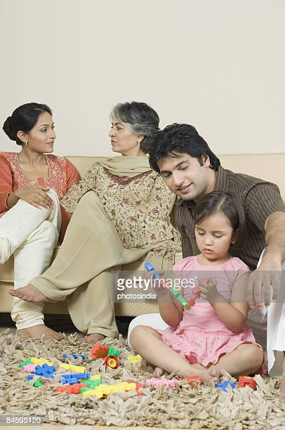 Family in a living room and girls playing game on a carpet