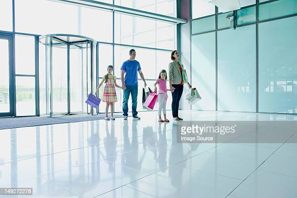 Family in airport with shopping bags