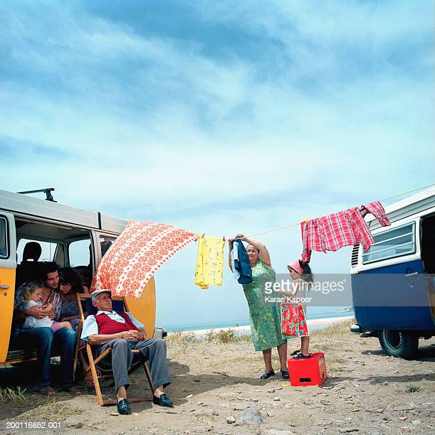 Family in and beside camper, mature woman hanging washing on line