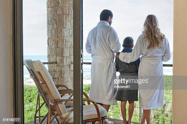 Family in bathrobes standing on patio of beach house