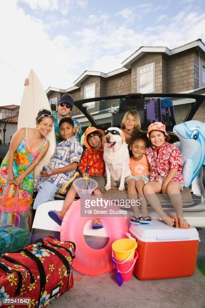 Family in beach gear at back of packed car