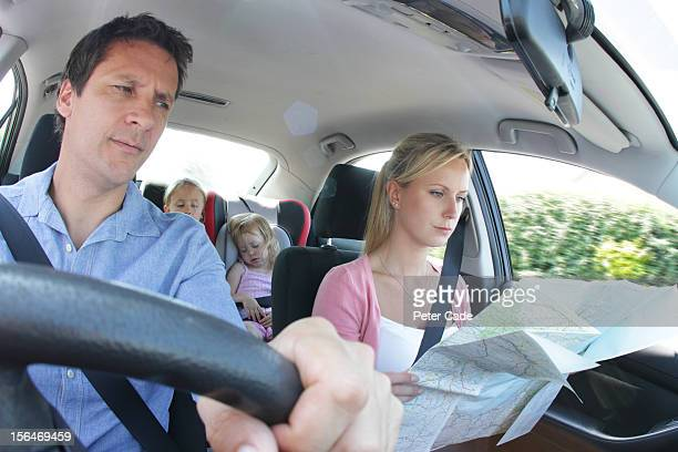 Family in car, children asleep, parents with map