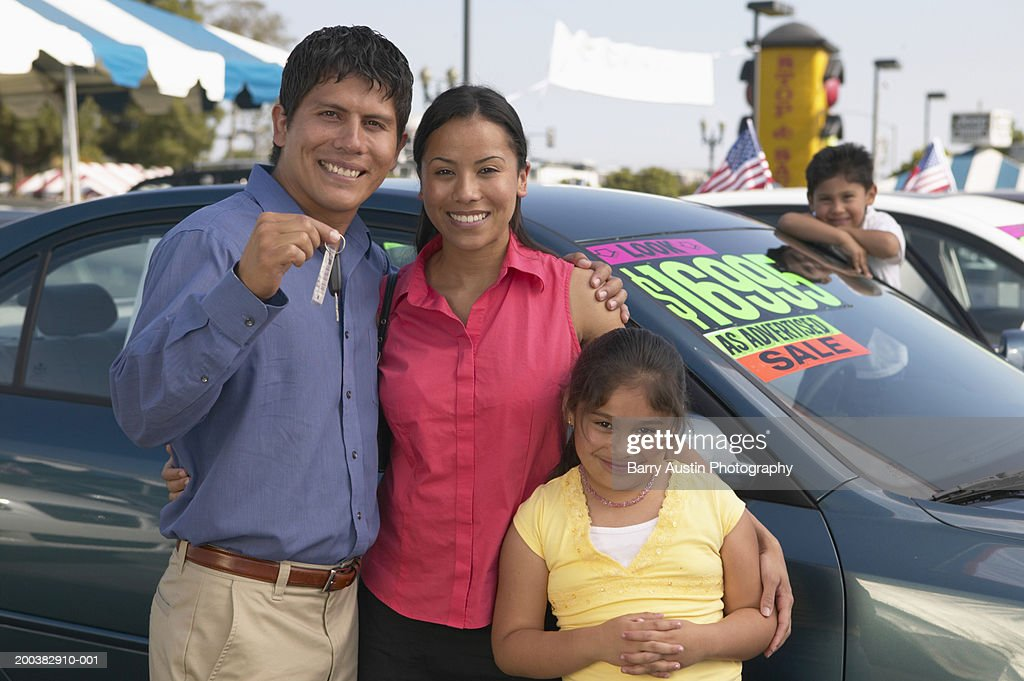 Family in car lot, father holding keys, smiling, portrait : Stock Photo