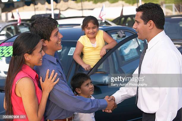 Family in car lot, father shaking hands with car salesman