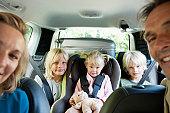 Family in car, smiling at camera
